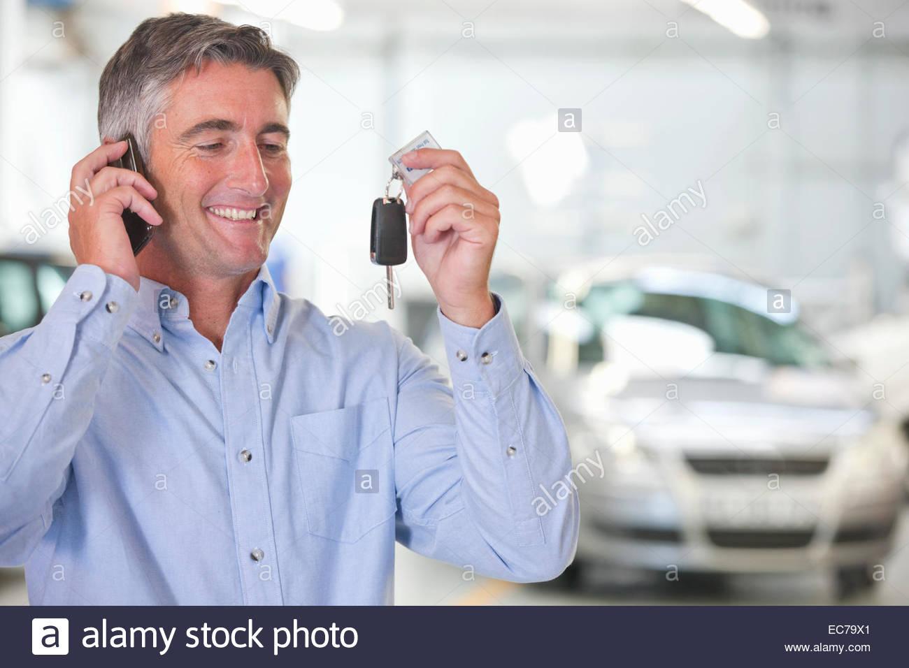 Mann auf dem Handy hält Autoschlüssel von Neuwagen Stockbild