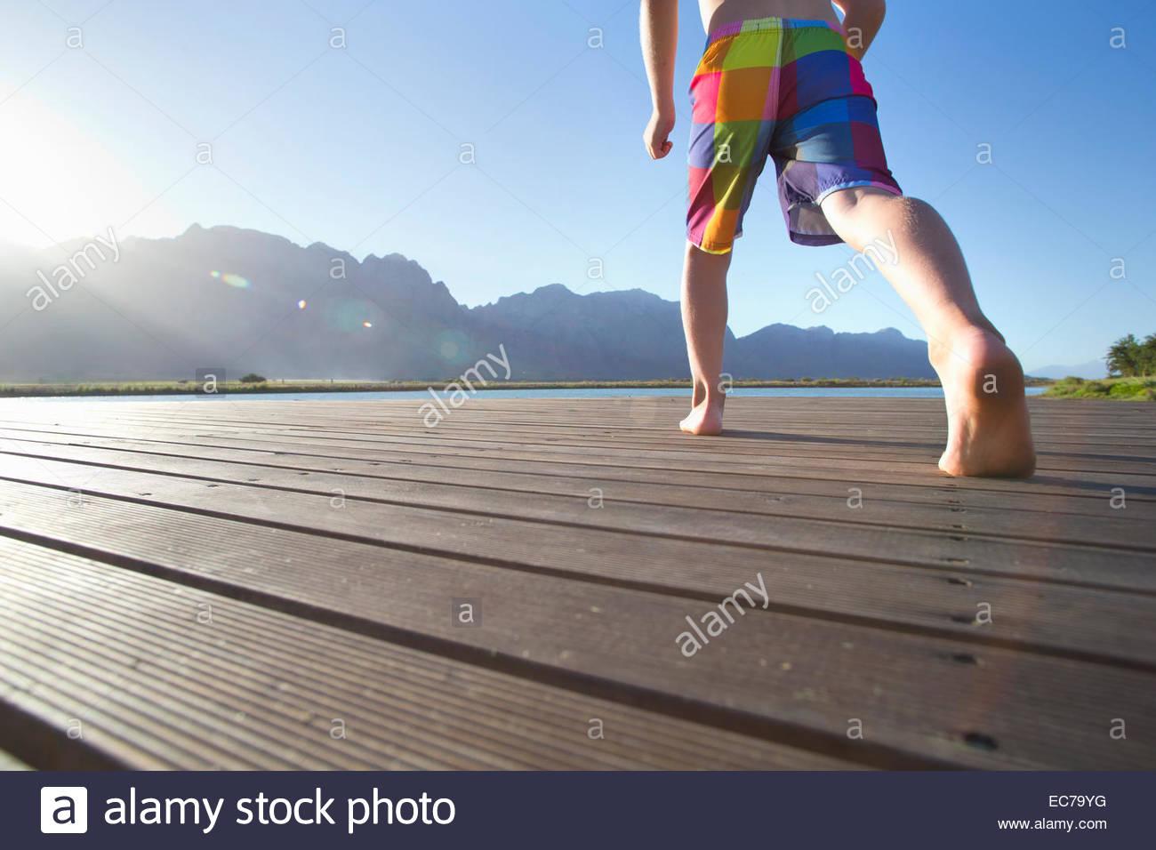 Junge laufen, um von einem Steg in den See springen Stockbild