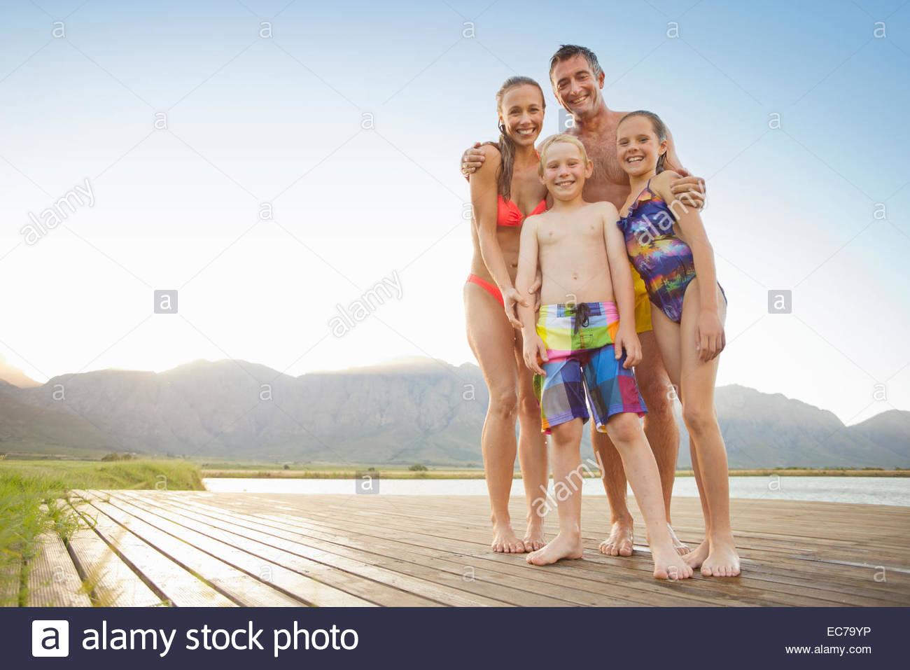 Familie in Badebekleidung am Holzsteg Stockbild