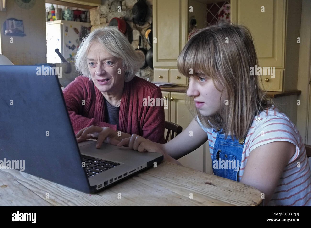 Ein 11 Jahres altes Mädchen lehrt ihrer Großmutter, wie man einen Computer verwenden Stockbild
