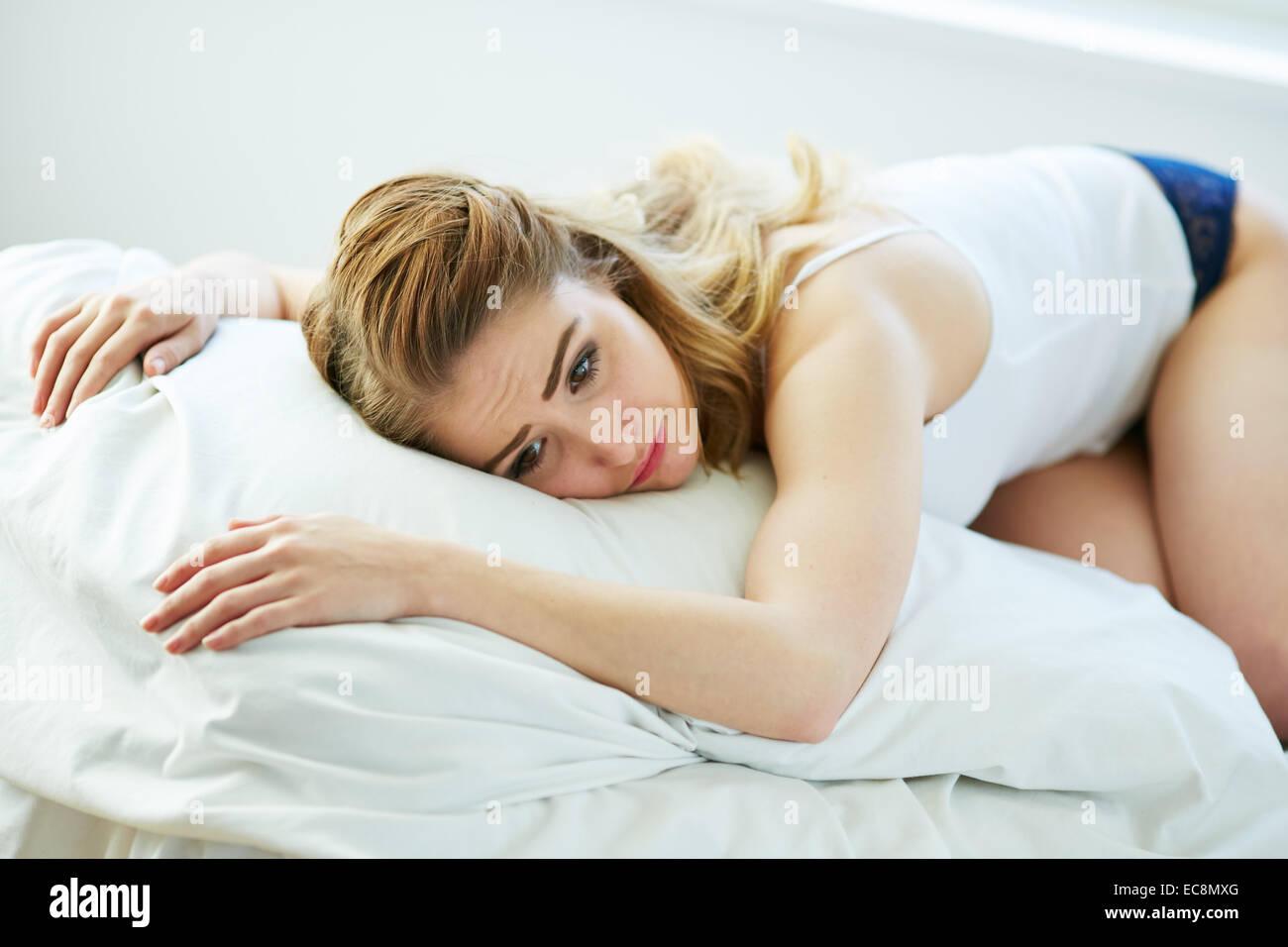 Aufgeregt Mädchen auf Bett liegend Stockbild