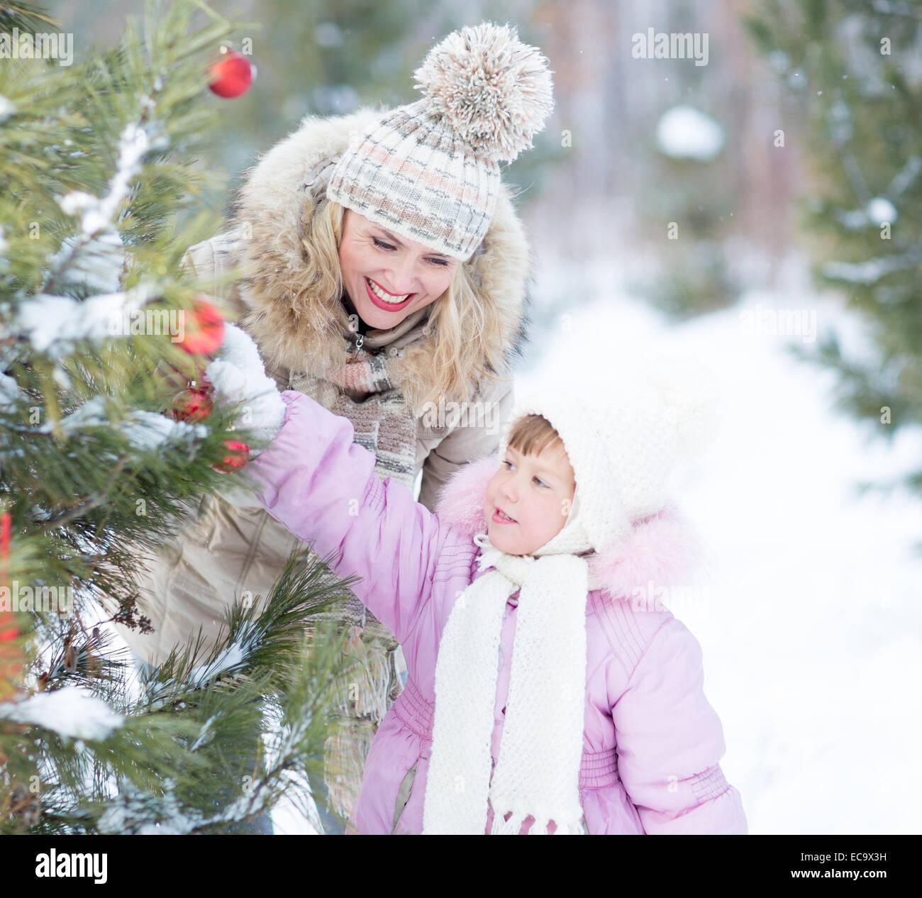 Glückliche Familie Mutter und Kind spielt mit Weihnachtsbaum Dekoration im freien Stockbild
