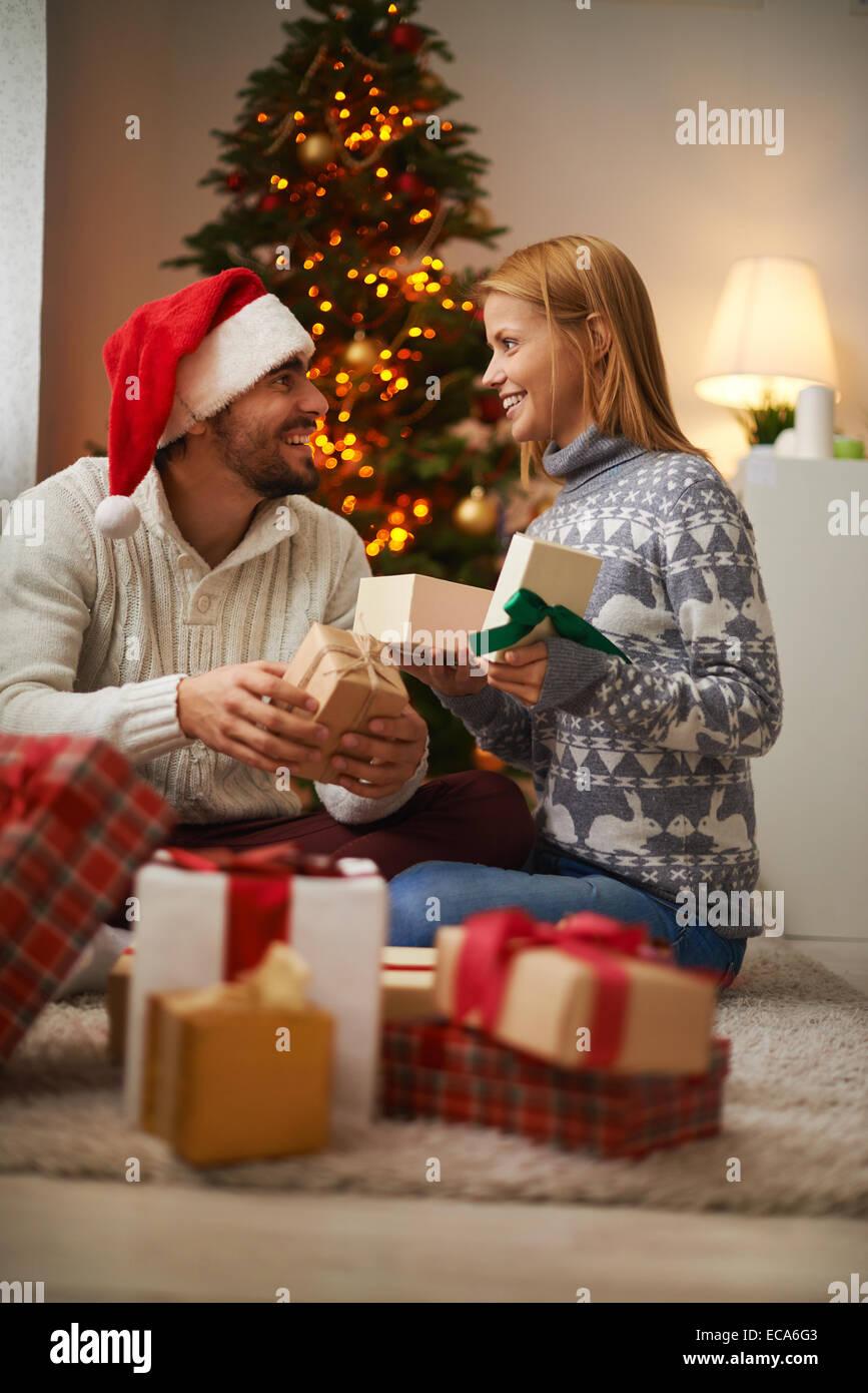 Fröhliches paar Pakete mit Eröffnung präsentiert auf Weihnachtsnacht Stockbild
