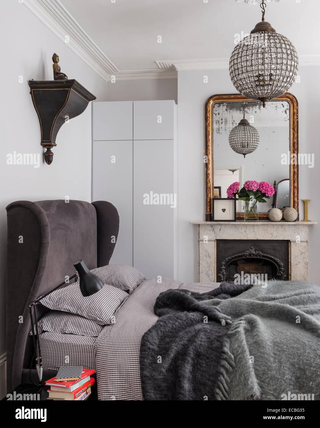 Luxus gepolsterten Bett vom Bridgepoint im Schlafzimmer mit Kamin, eingebauten Speicher und Schuld gerahmten Spiegel. Stockbild