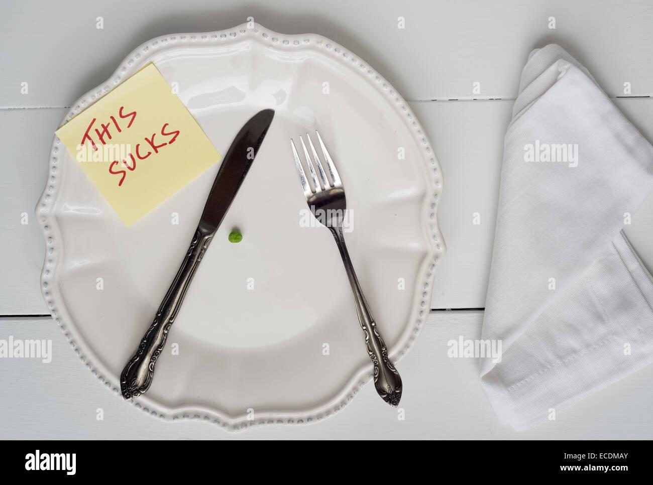 Gewicht Verlust Neujahrs Konzept - einzelne Erbsen auf einem Teller mit dieser saugt Hinweis Stockbild