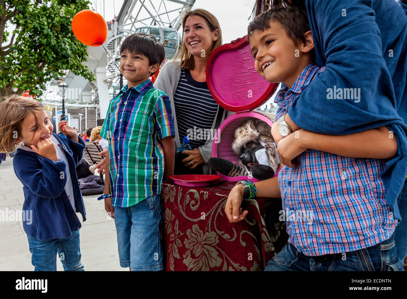 Eine Familie posiert mit A Street Entertainer auf der South Bank, London, England Stockfoto