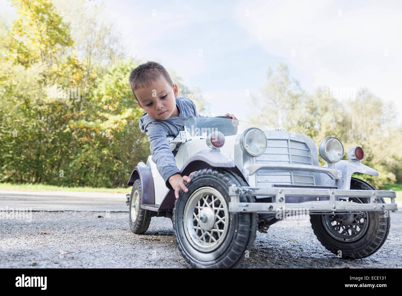 Kleiner Junge Porträt überprüfen Reifen Modell Oldtimer Stockbild