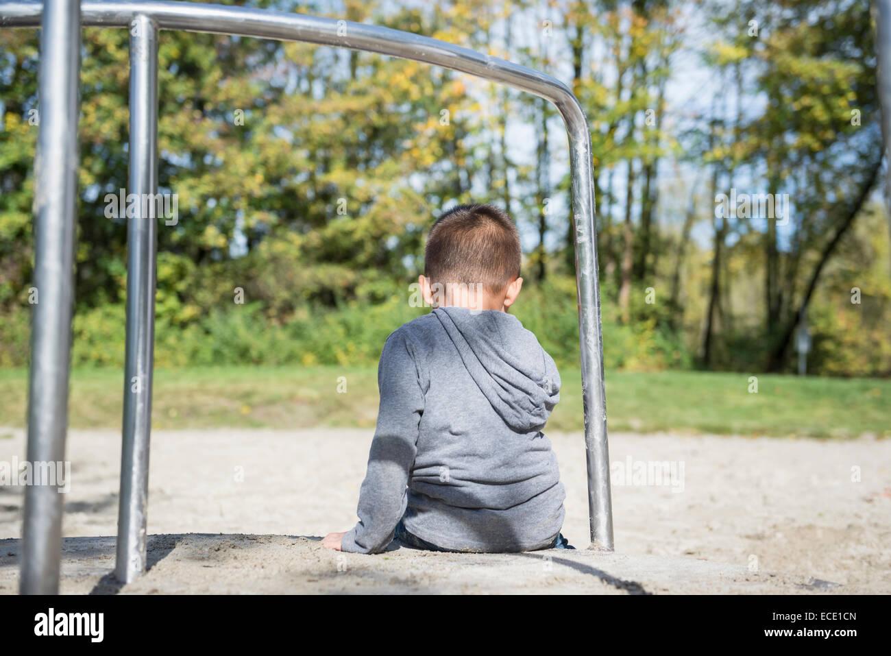 Kleine einsame junge sitzt alleine auf Spielplatz Stockbild