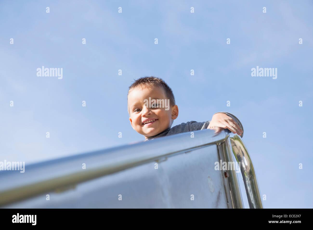 Spielplatz kleiner Junge hoch oben Porträt Folie Metall Stockfoto