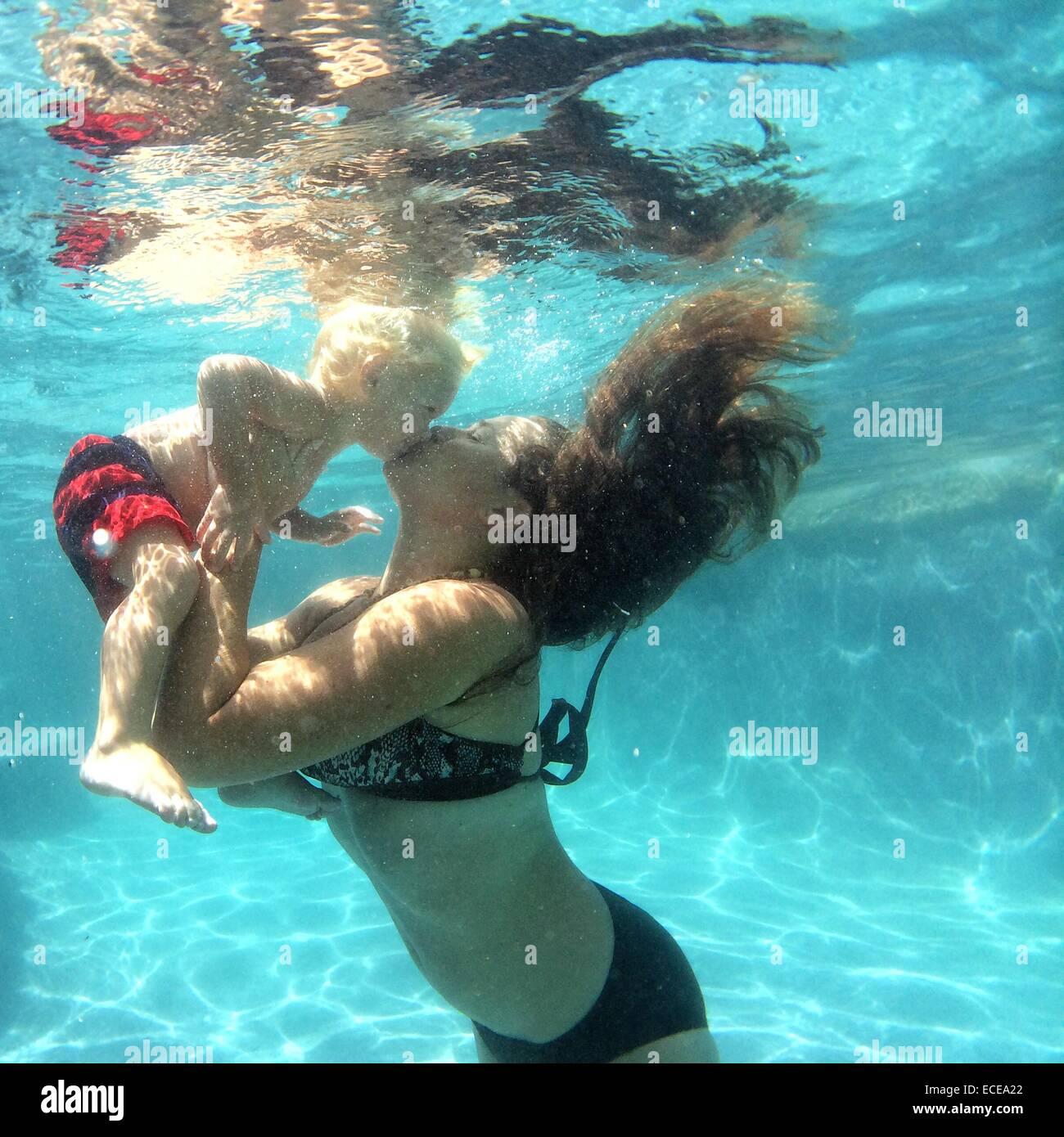 Mutter küssen Baby Boy unter Wasser Stockbild