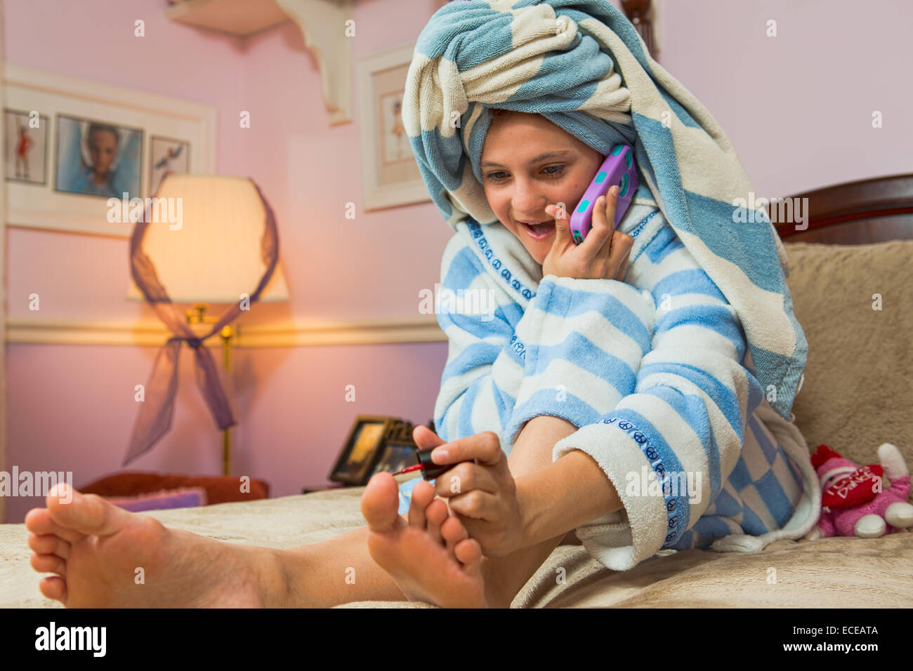 Mädchen sitzen auf Bett telefonieren mit Handy während der Malerei Zehennägel Stockbild