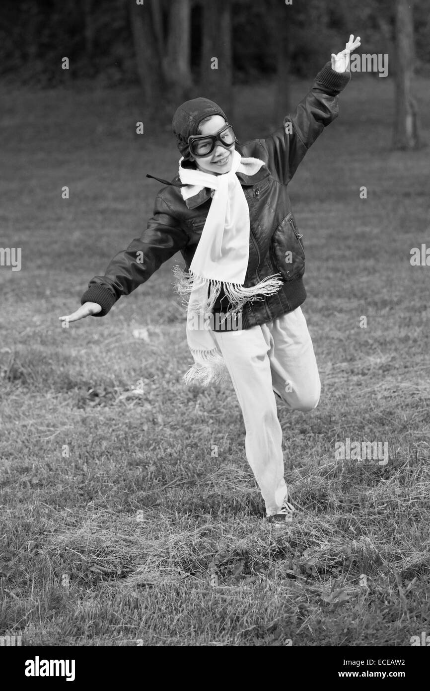 Junge läuft mit Arme ausgestreckt vorgibt, fliegen Stockbild