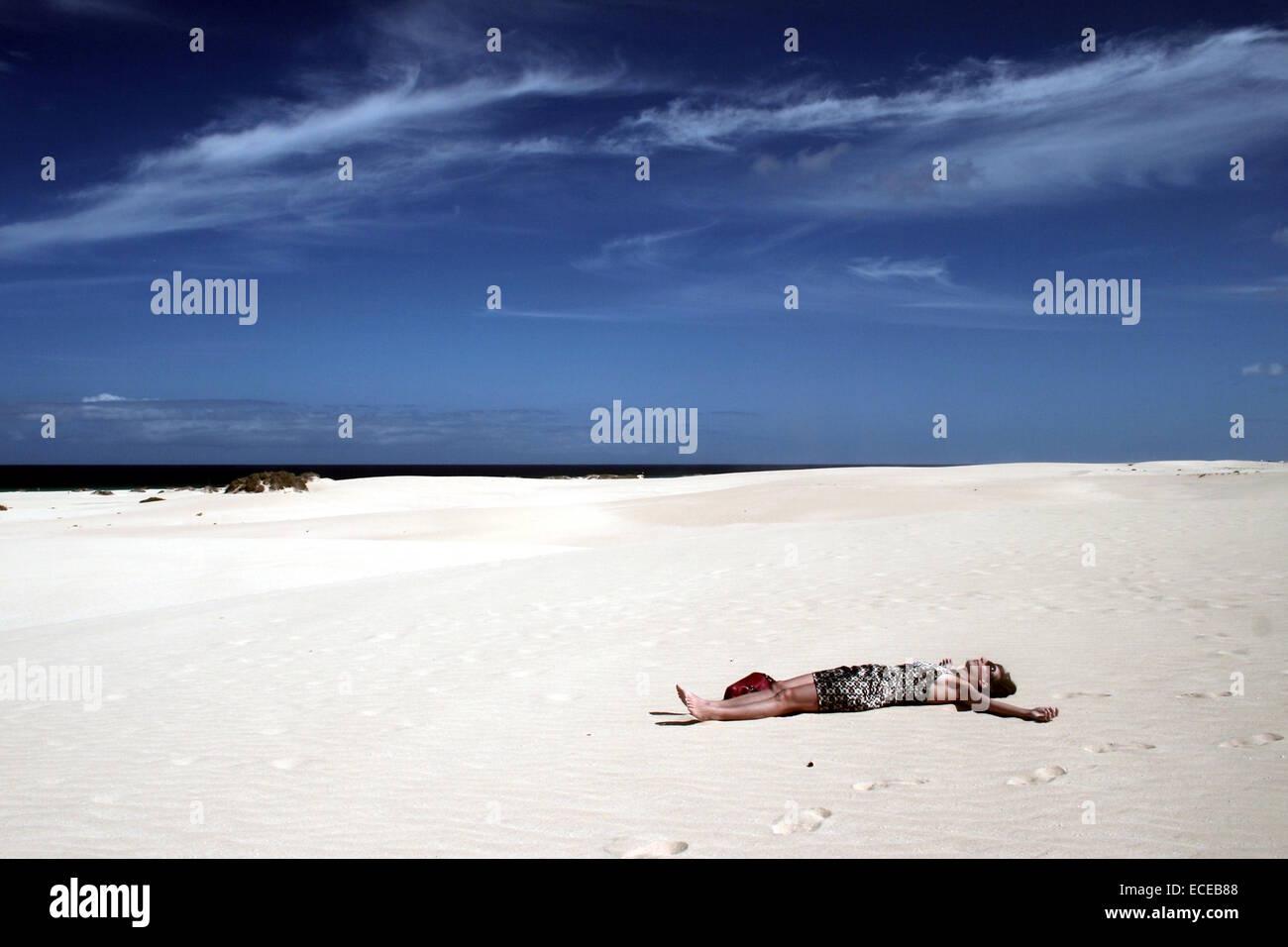 Spanien, Kanarische Inseln, Fuerteventura, Natur Park der Dünen von Corralejo, Frau liegt in der Wüste Stockbild