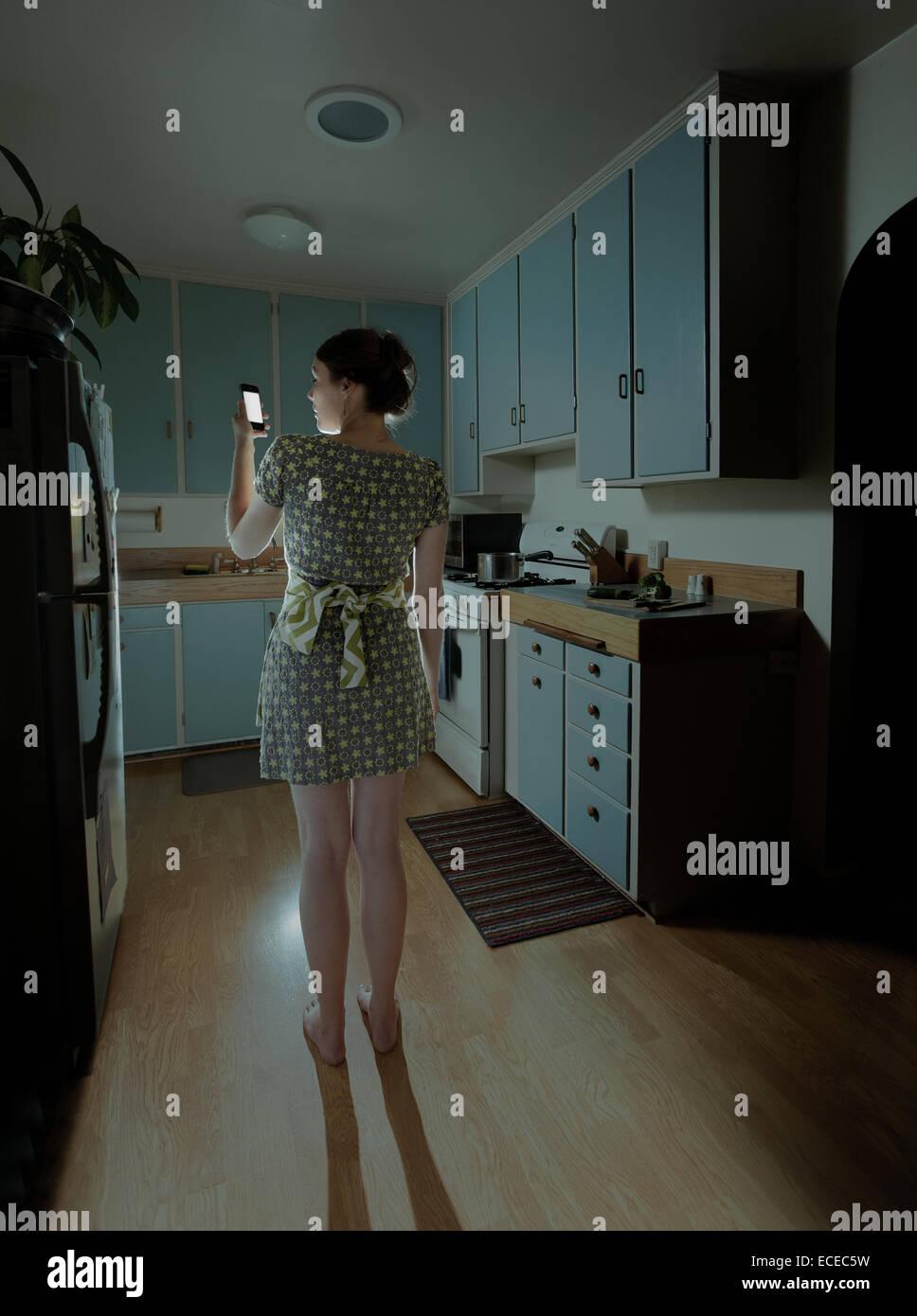 Frau mit Smartphone in Küche in der Nacht Stockbild