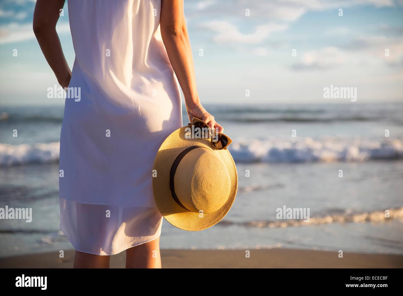 Rückansicht der Frau im weißen Kleid am Strand stehen und halten Hut Stockbild