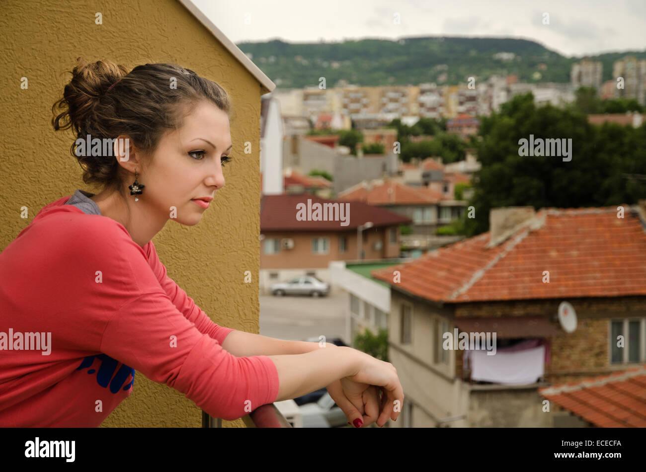 Frau auf einem Balkon stehend Stockbild