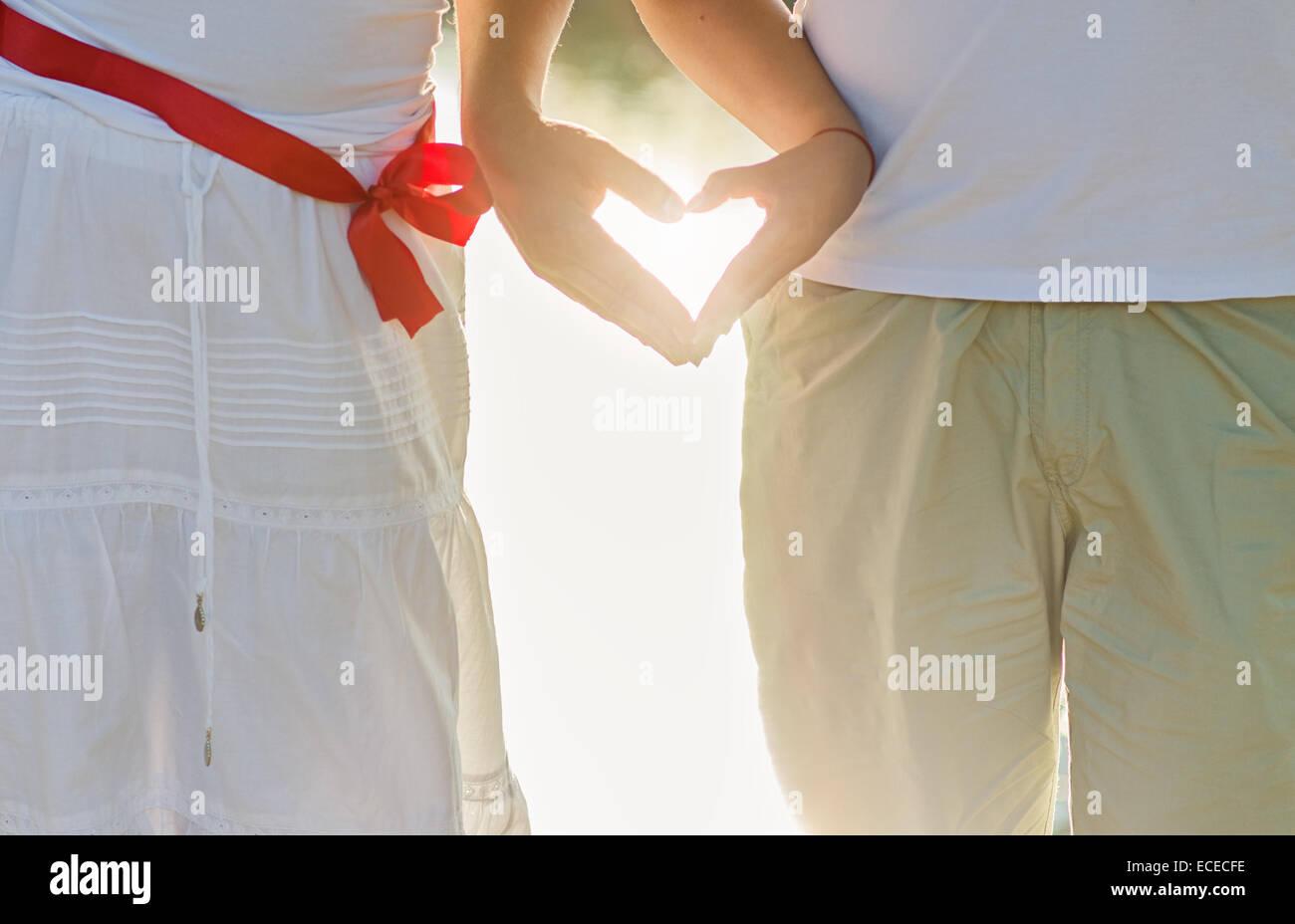 Hände von zwei Menschen, die die Form des Herzens Stockbild
