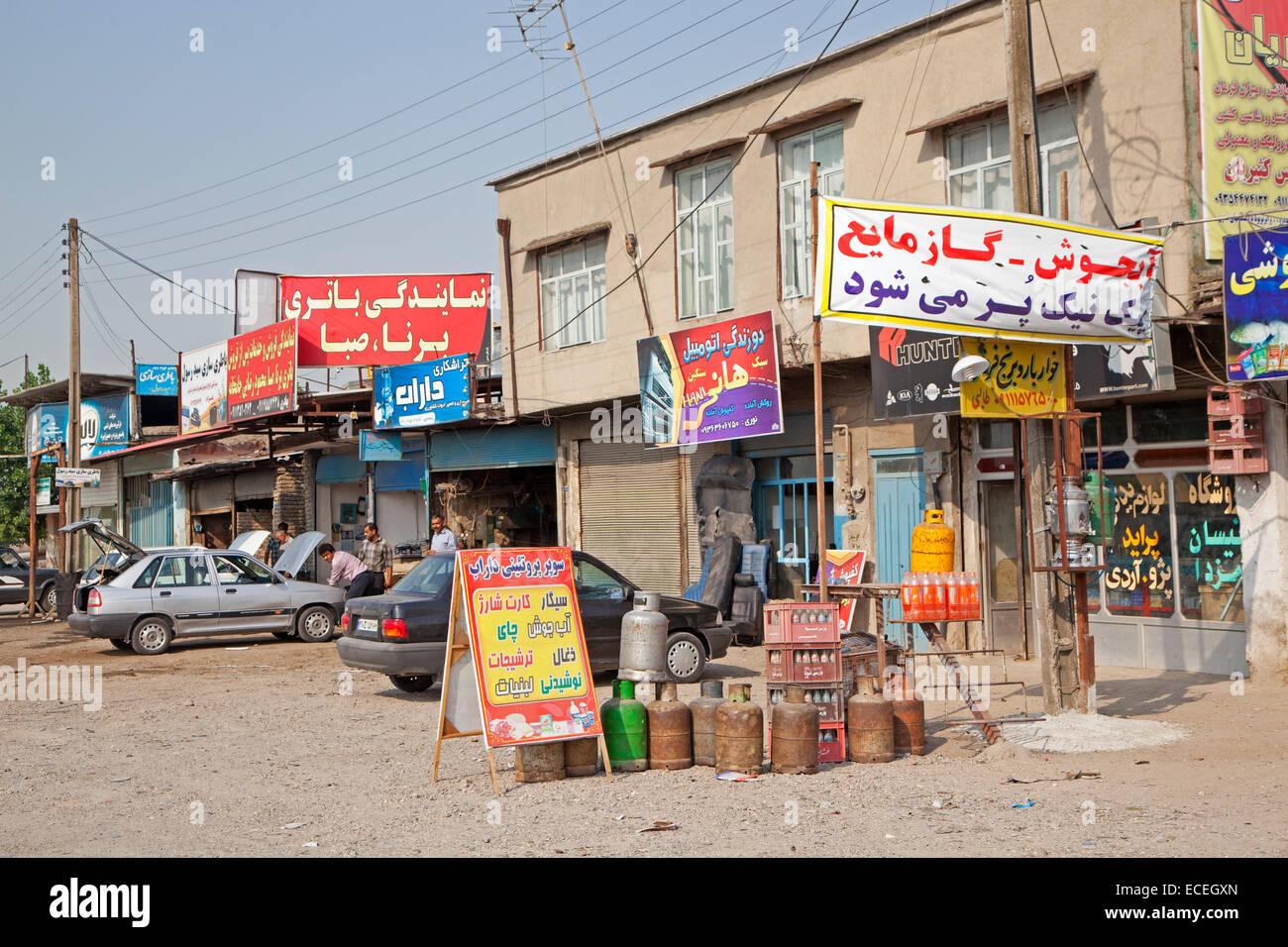 Iraner, die Arbeiten am Auto in primitiven Garage, Autowerkstatt und Lebensmittelgeschäft im Dorf im Iran Stockbild