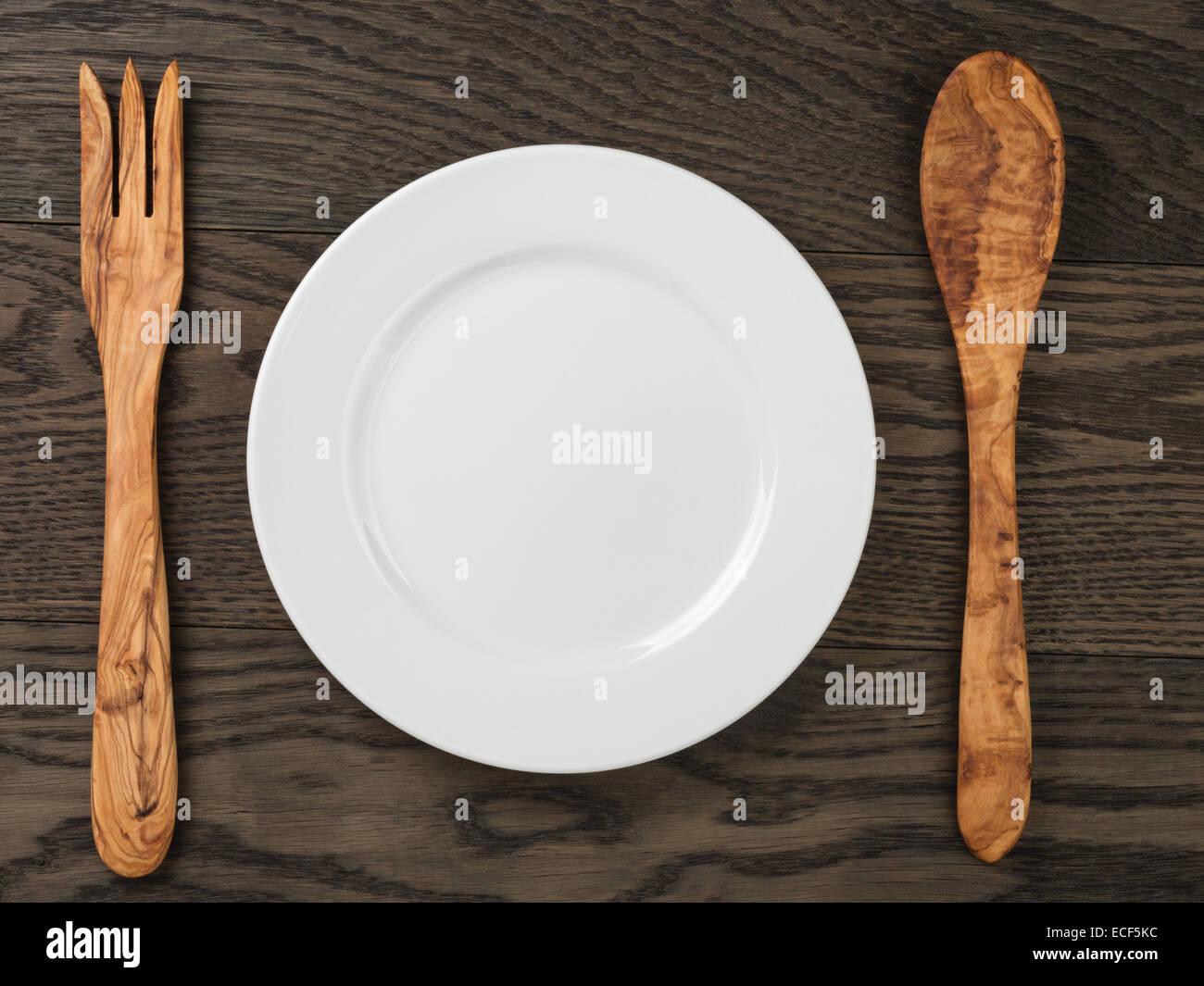 leeren weißen Teller mit Holz Gabel und Löffel auf Eichentisch ...