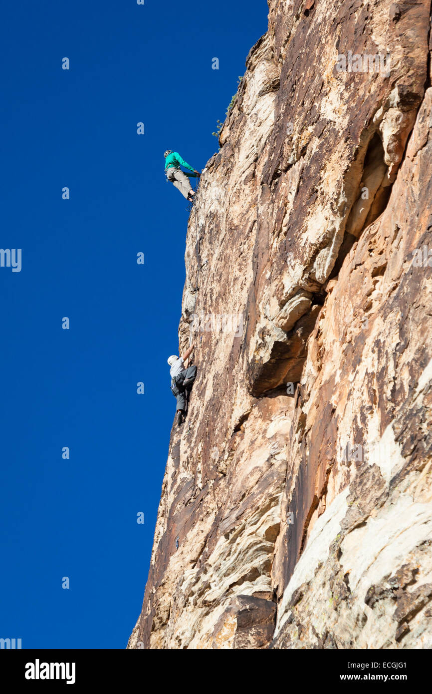 junger Mann Klettern ein Sandstein mit der notwendigen Sicherheit Ausrüstung Stockbild