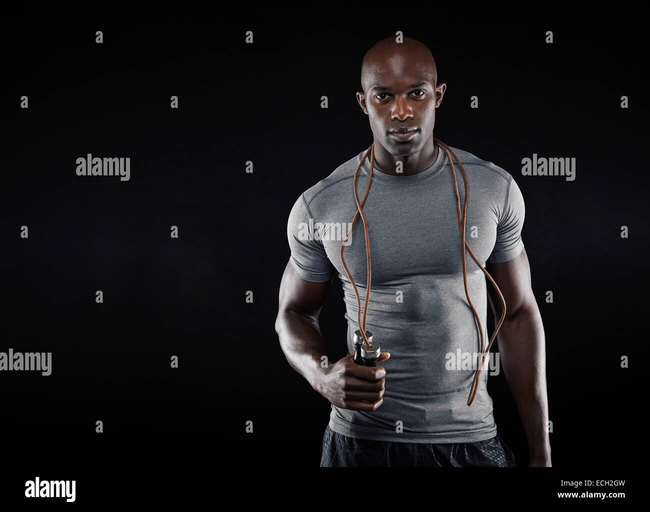 Schöner muskulöser Mann mit Seilspringen auf schwarzem Hintergrund. Passen Sie afrikanisches Modell mit Stockbild