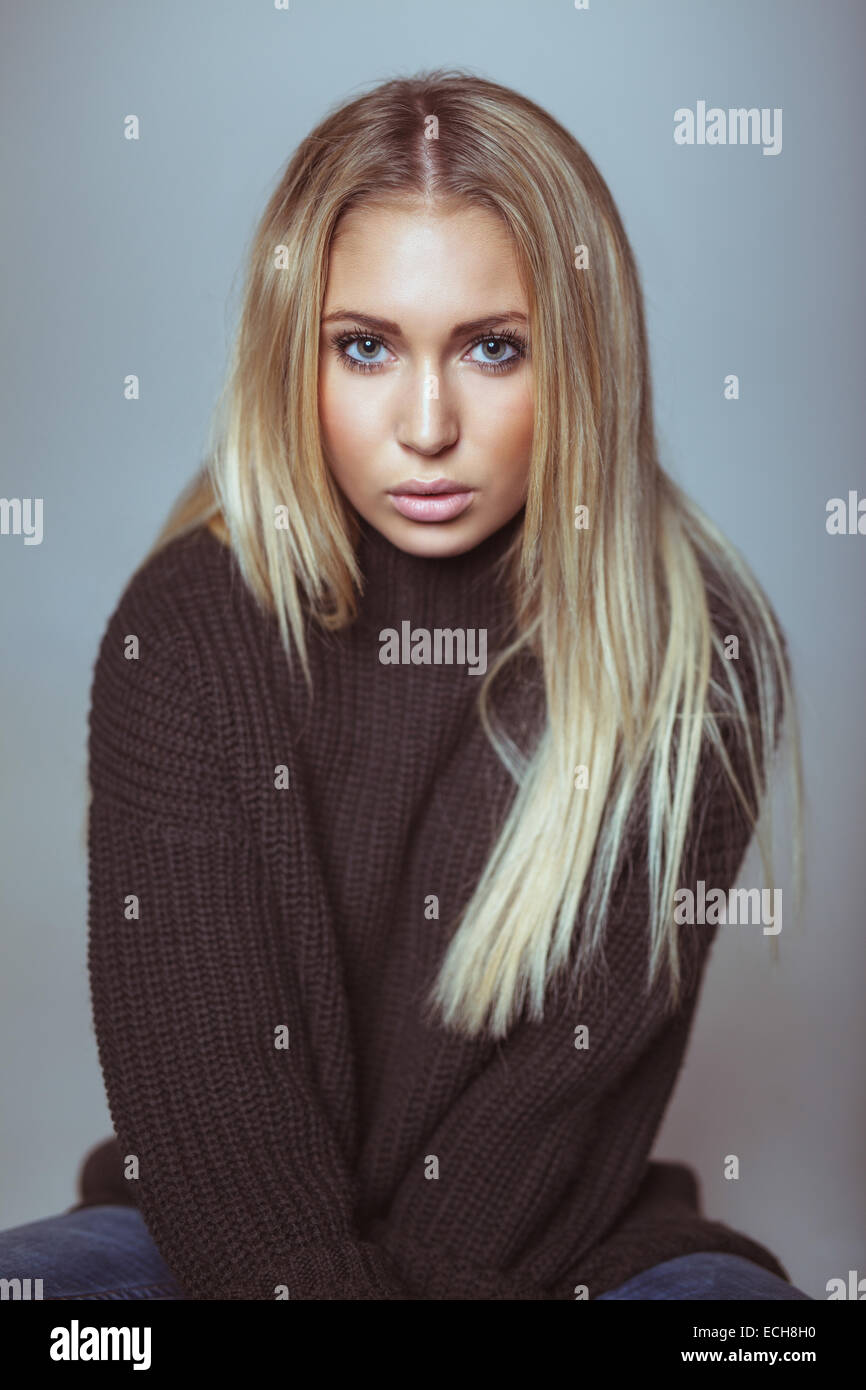 Porträt von schöne junge blonde Frau in Pullover Blick in die Kamera. Kaukasische weibliches Modell gegen Stockbild