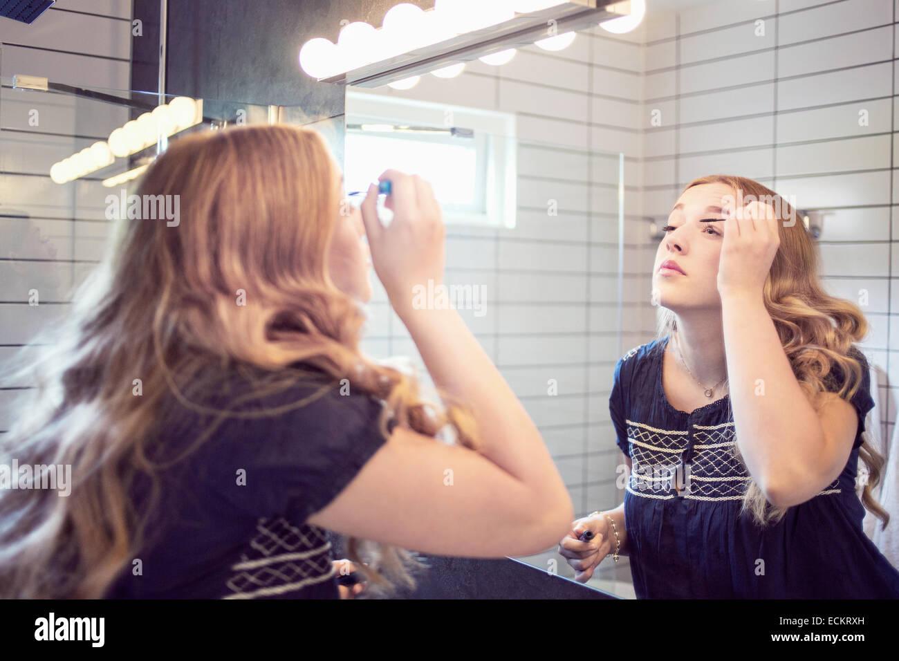 Junge Frau, die Anwendung von Mascara vor Badezimmerspiegel Stockbild