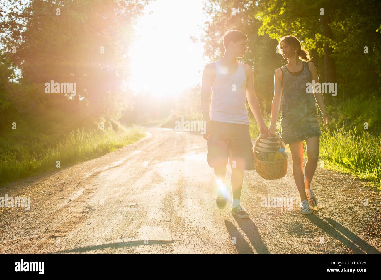Voller Länge Vorderansicht des Paares zu Fuß auf Feldweg gegen die helle Sonne Stockbild