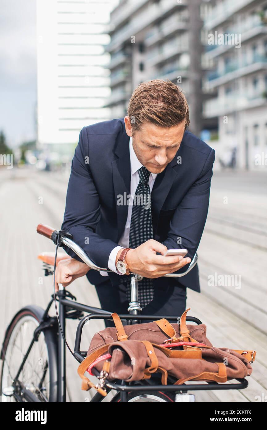Geschäftsmann mit Smartphone in Stadt und stützte sich auf dem Fahrrad Stockfoto