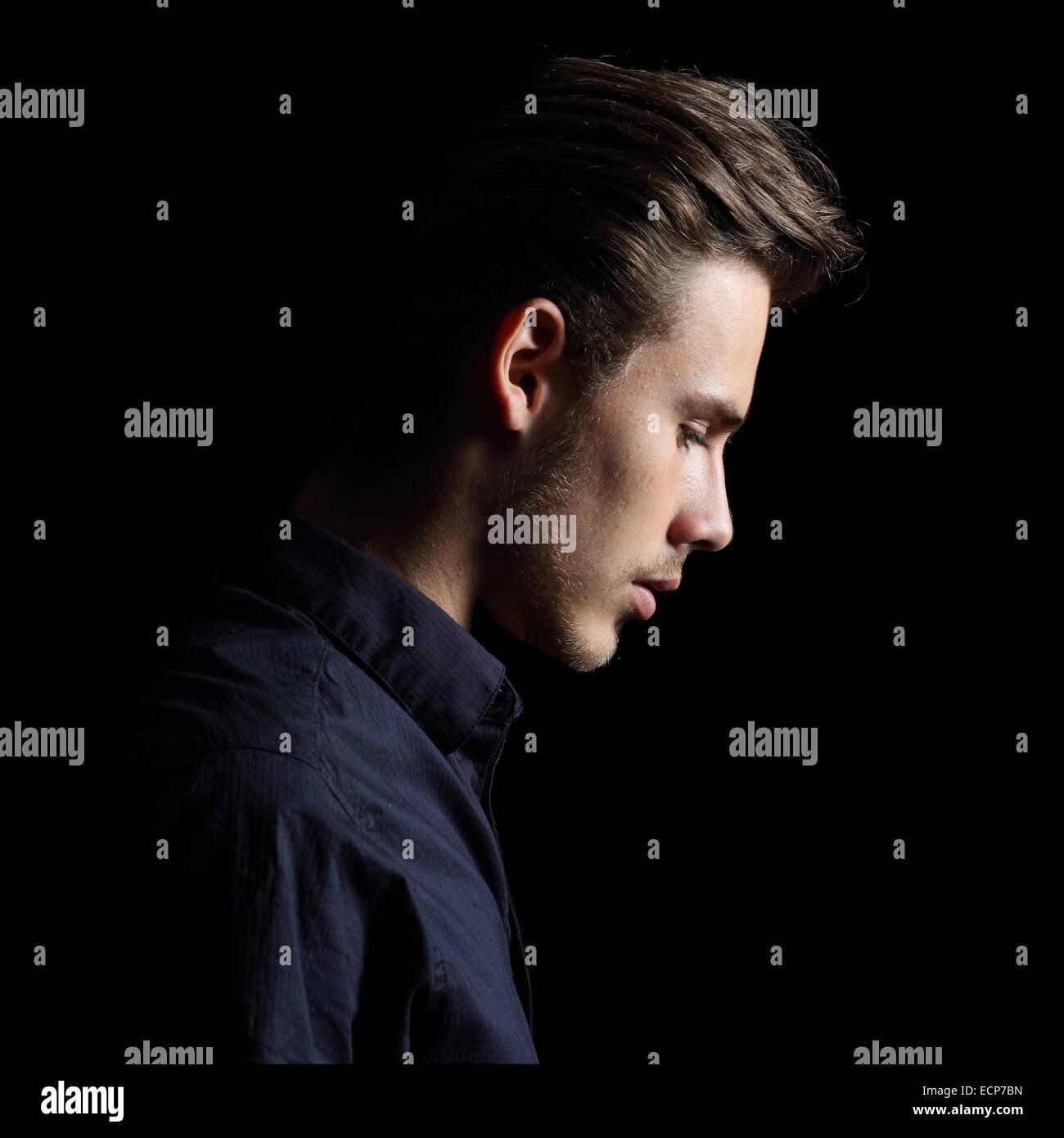 Profil von ein trauriger Mann Gesicht kleinlaut auf schwarz auf schwarzem Hintergrund isoliert Stockbild
