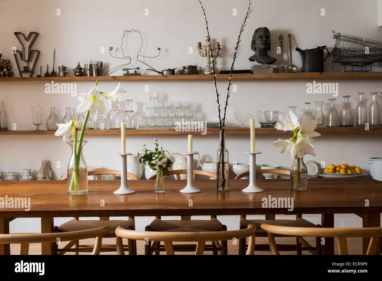 Lilien und Kerzen auf große Bauernhaus Esstisch mit Holzstühlen im stilvollen Speisesaal mit offenen Regalen Stockbild