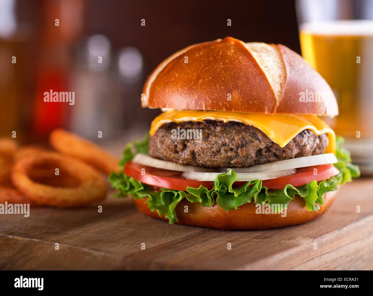 Ein köstliches Gourmet-Cheeseburger auf einem Brezel-Brötchen mit Salat, Zwiebel und Tomate. Stockbild