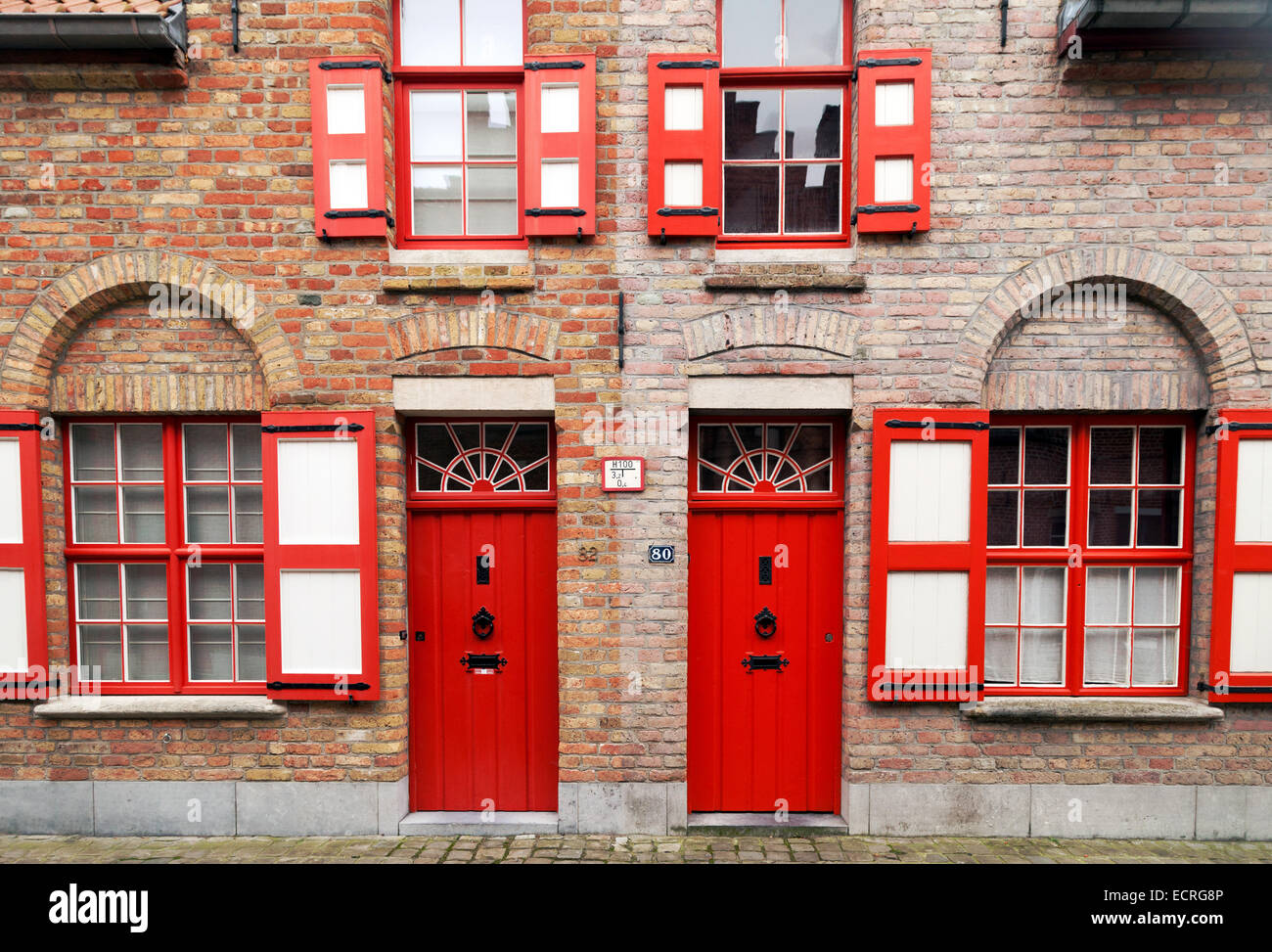 Zwei rote Reihenhäuser in Brügge, Belgien, Europa, Begriff der Symmetrie oder Reflexion Stockbild