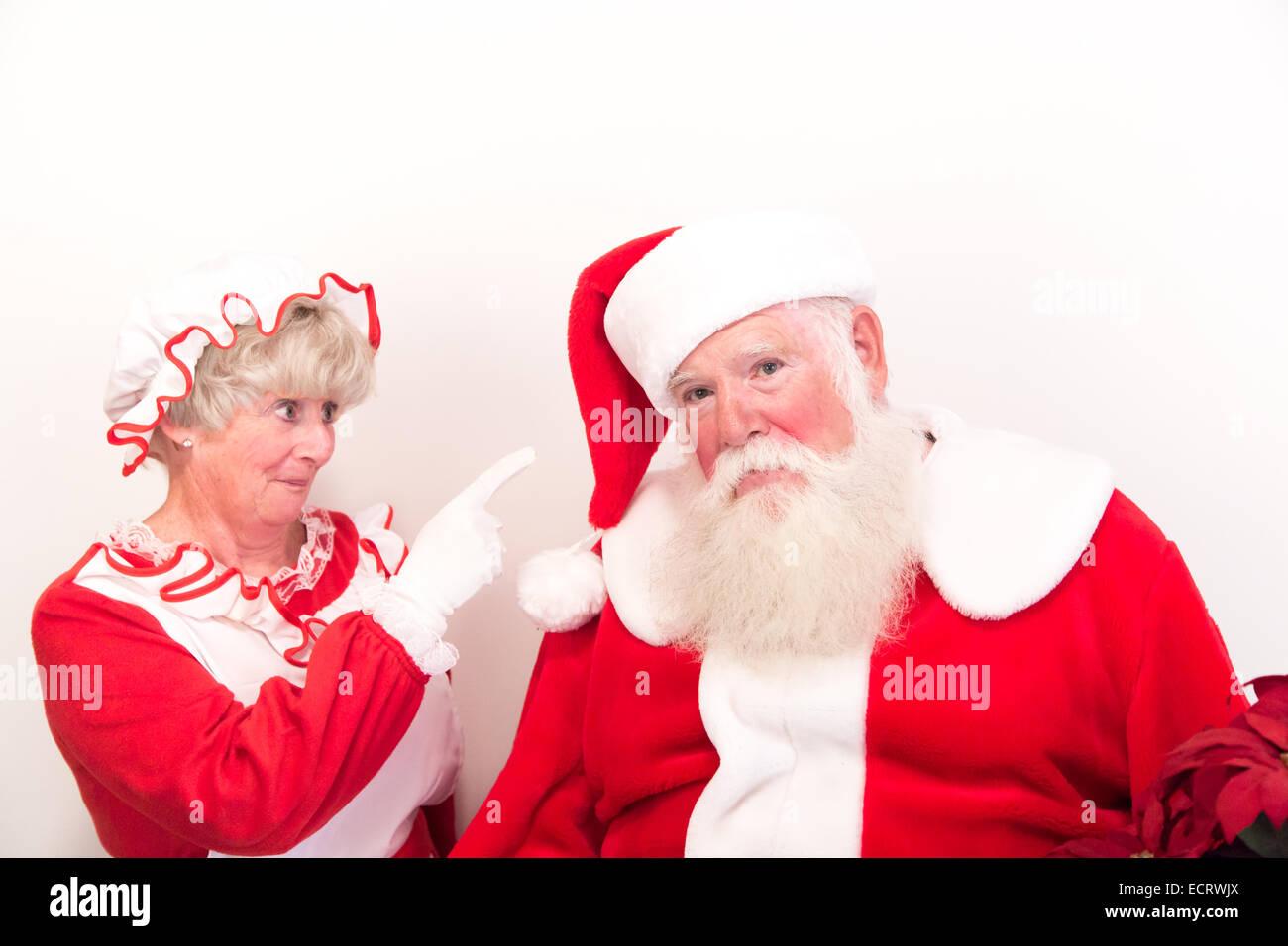Ein traurig und mürrisch Weihnachtsmann wird von Frau Claus gescholten. Stockbild