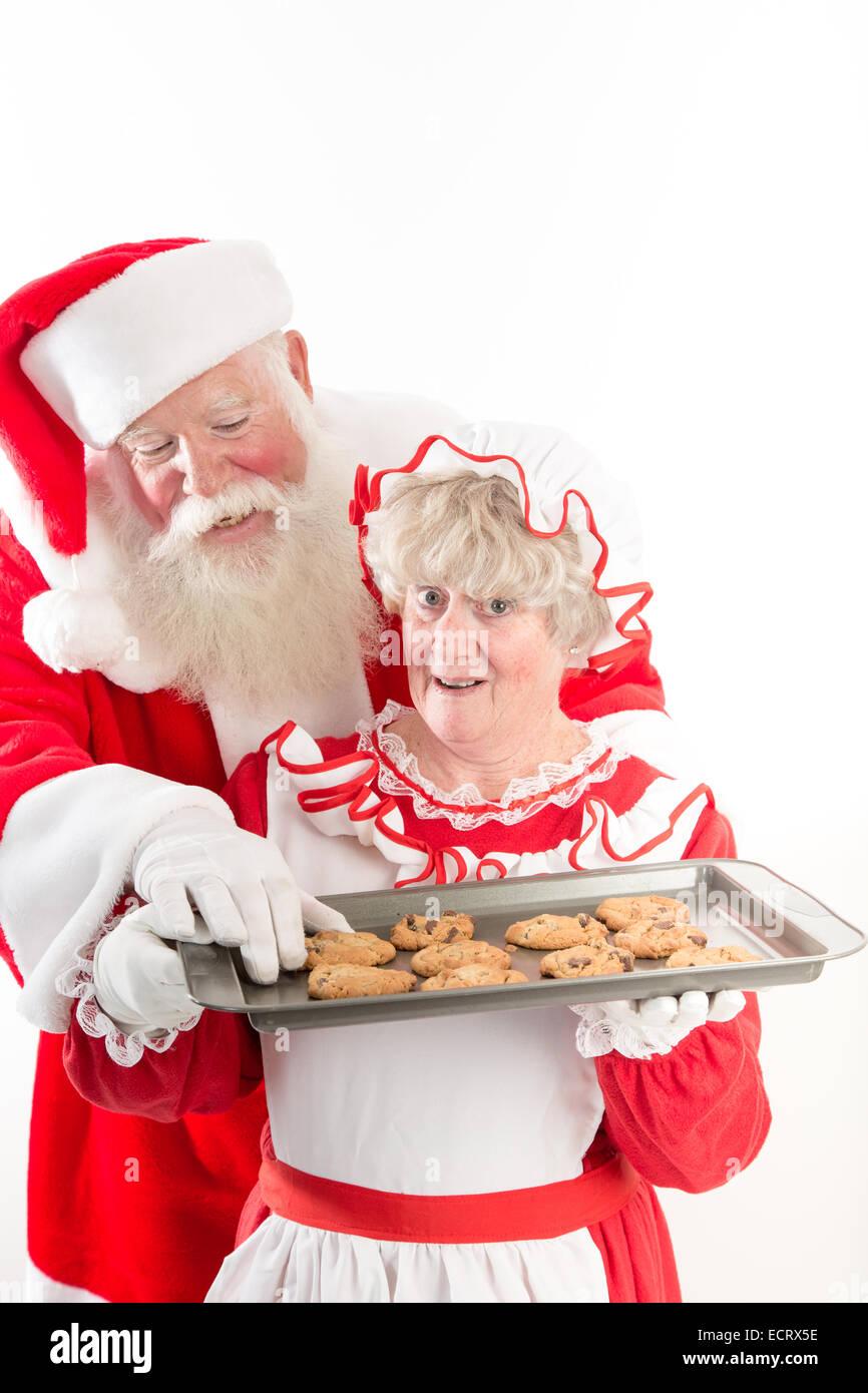 Santa stiehlt einen warmen Cookie aus Frau Claus Fach. Stockbild