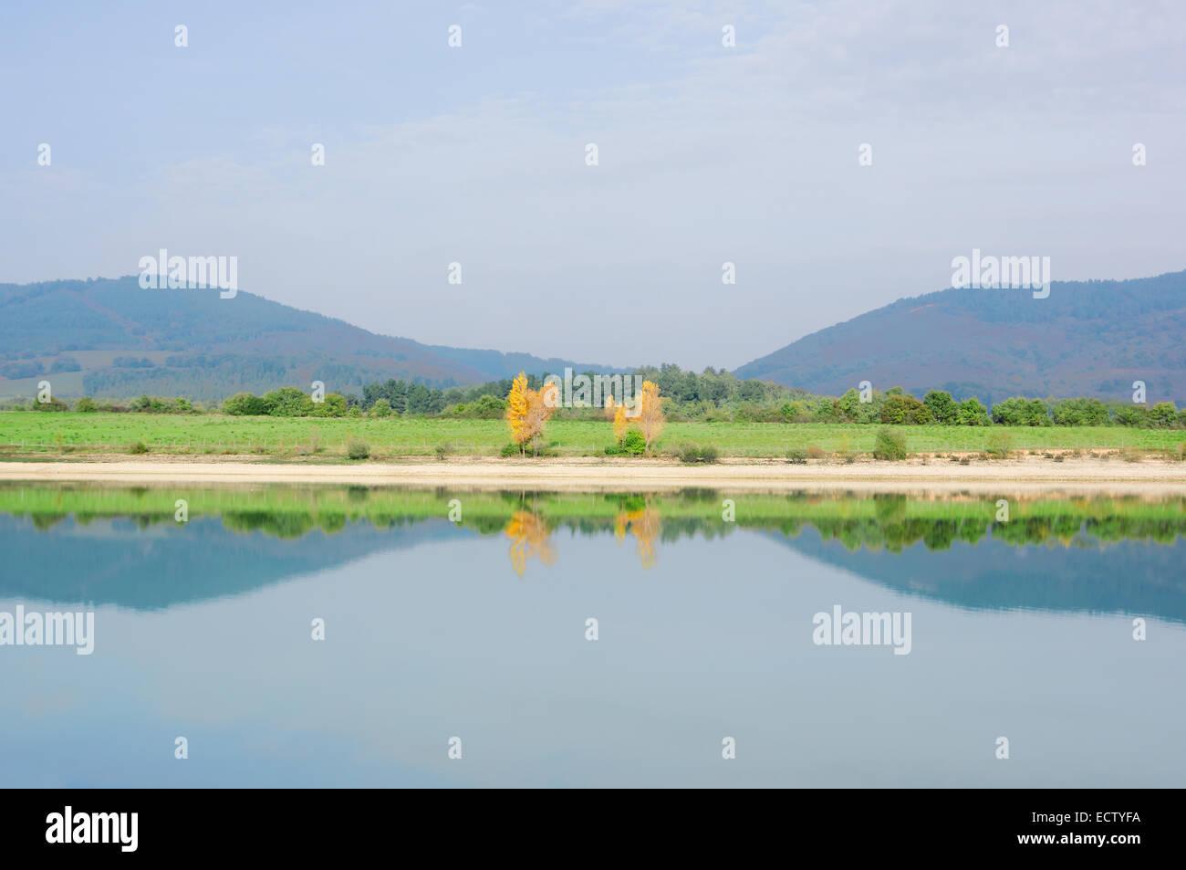 Symmetrie mit Baum Reflexionen auf einem See. Ullibarri Ganboa Stockbild