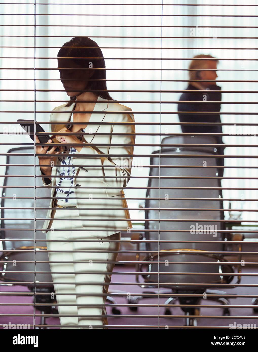 Geschäftsfrau mit Tablet pc stehen im Konferenzraum hinter Jalousien Stockbild