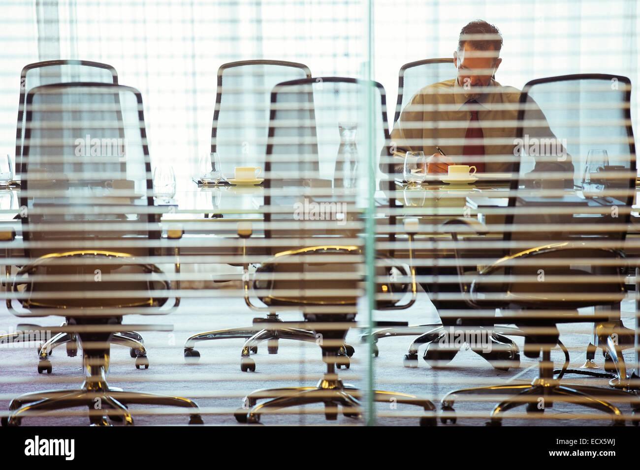 Geschäftsmann, sitzen hinter Jalousien im Konferenzraum Stockbild