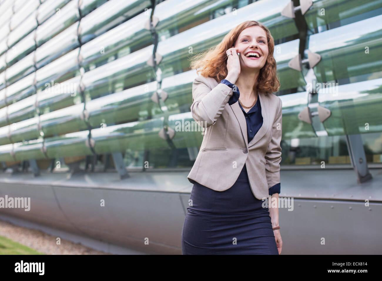 Geschäftsfrau, die am Handy im freien sprechen Stockbild