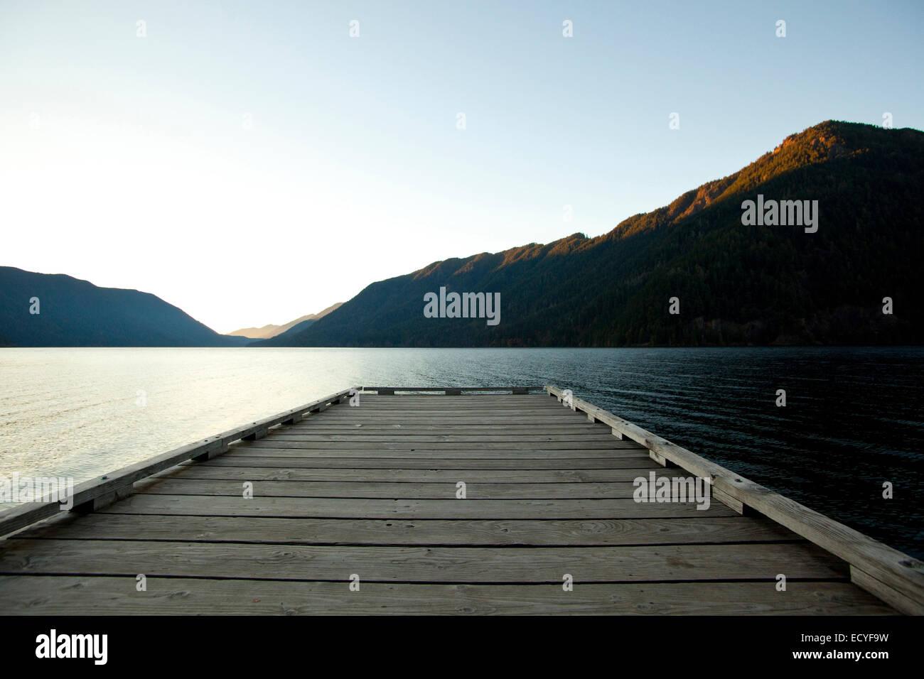 Holzdeck am See unter blauem Himmel Stockbild
