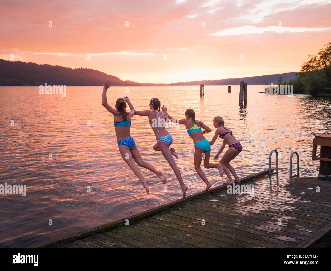 Mädchen aus hölzernen Dock in See springen Stockfoto