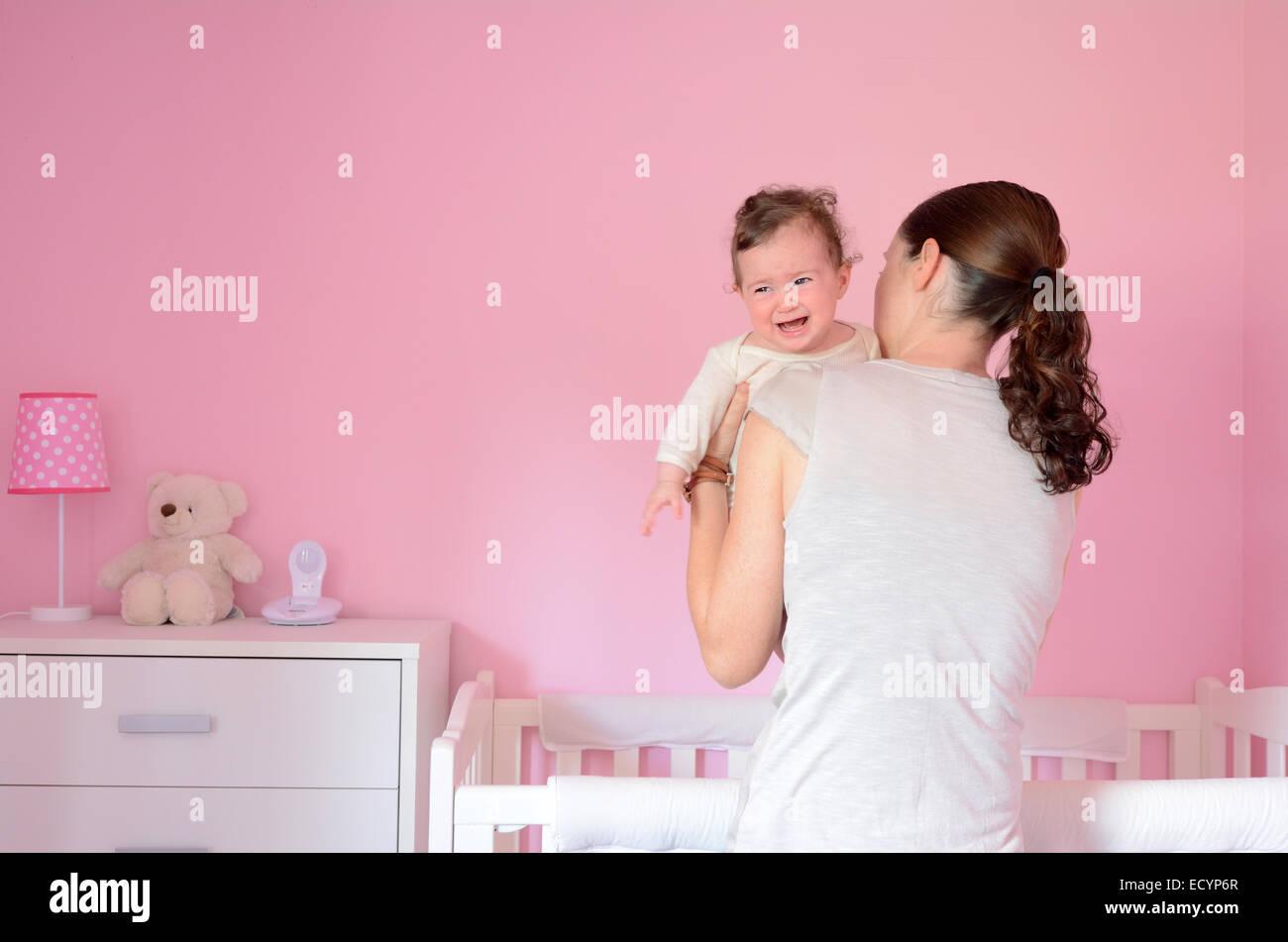 Junge Mutter setzt ihr Baby (Alter des Mädchens 06 Monate) zu schlafen, während sie schreit. Konzept Foto Stockbild