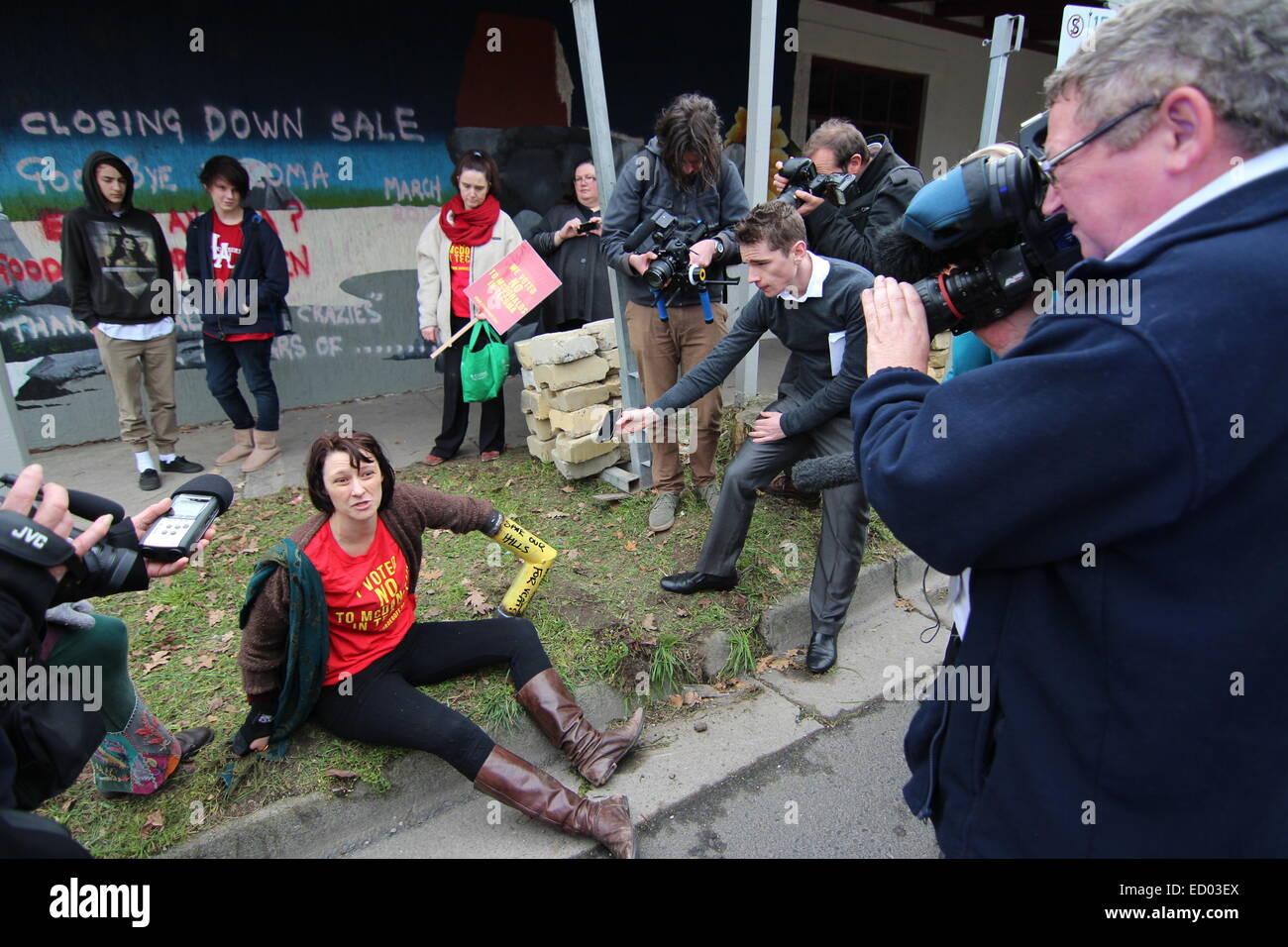 Demonstrant mit Spannvorrichtung am Arm, da sie von Medien und Journalisten umgeben ist. Stockbild