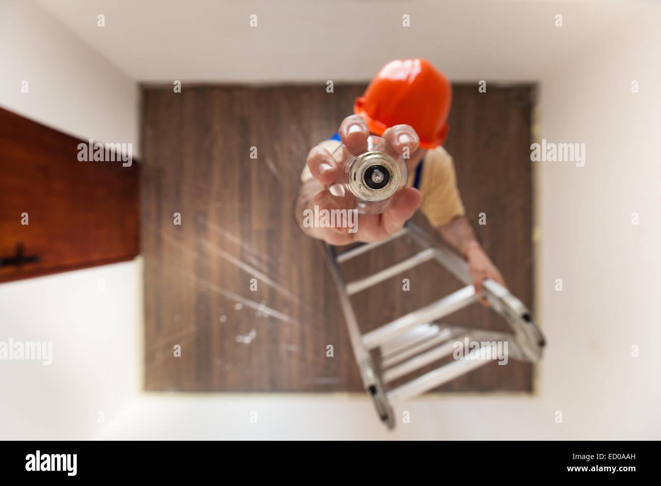 Elektriker auf der Leiter ist eine ausgebrannte Glühbirne wechseln. Stockbild