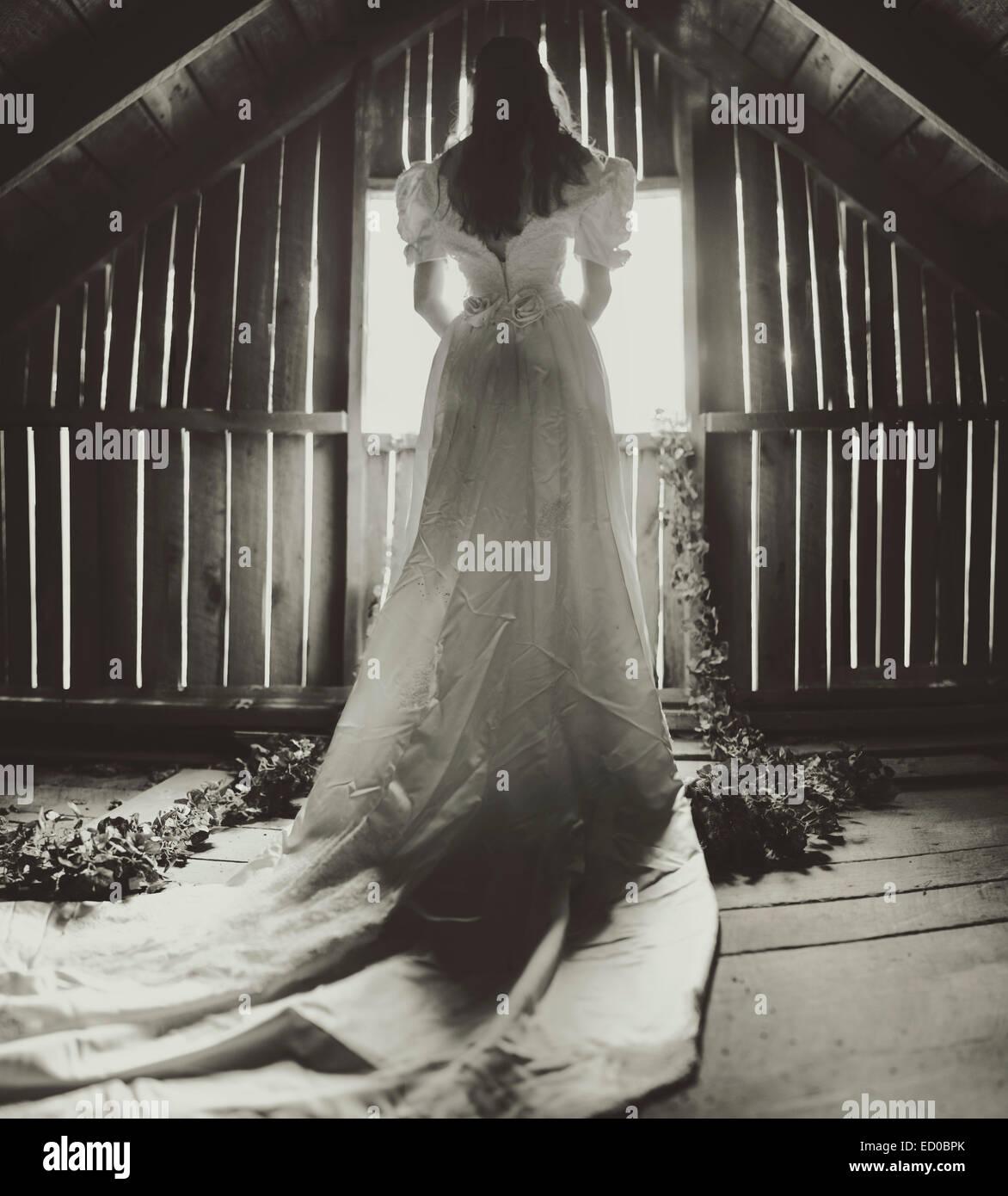 Rückansicht des junge Frau im Hochzeitskleid auf Dachboden Stockbild