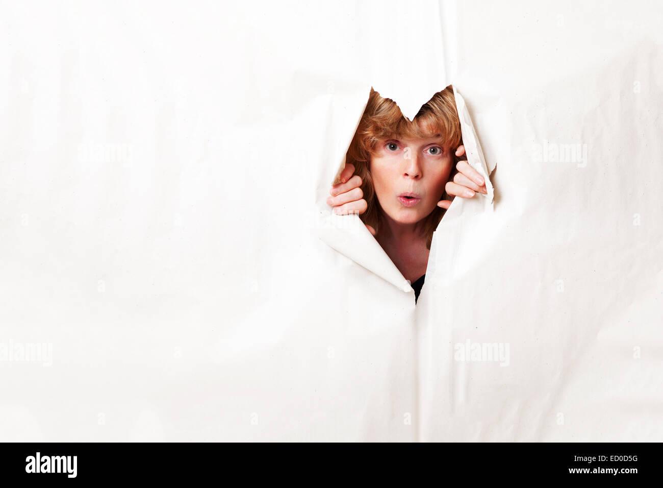 Frau auf der Suche durch zerrissenes Papier Stockbild