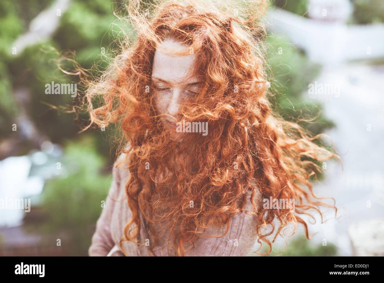 Porträt der jungen Frau mit langen, lockigen roten Haaren Stockbild