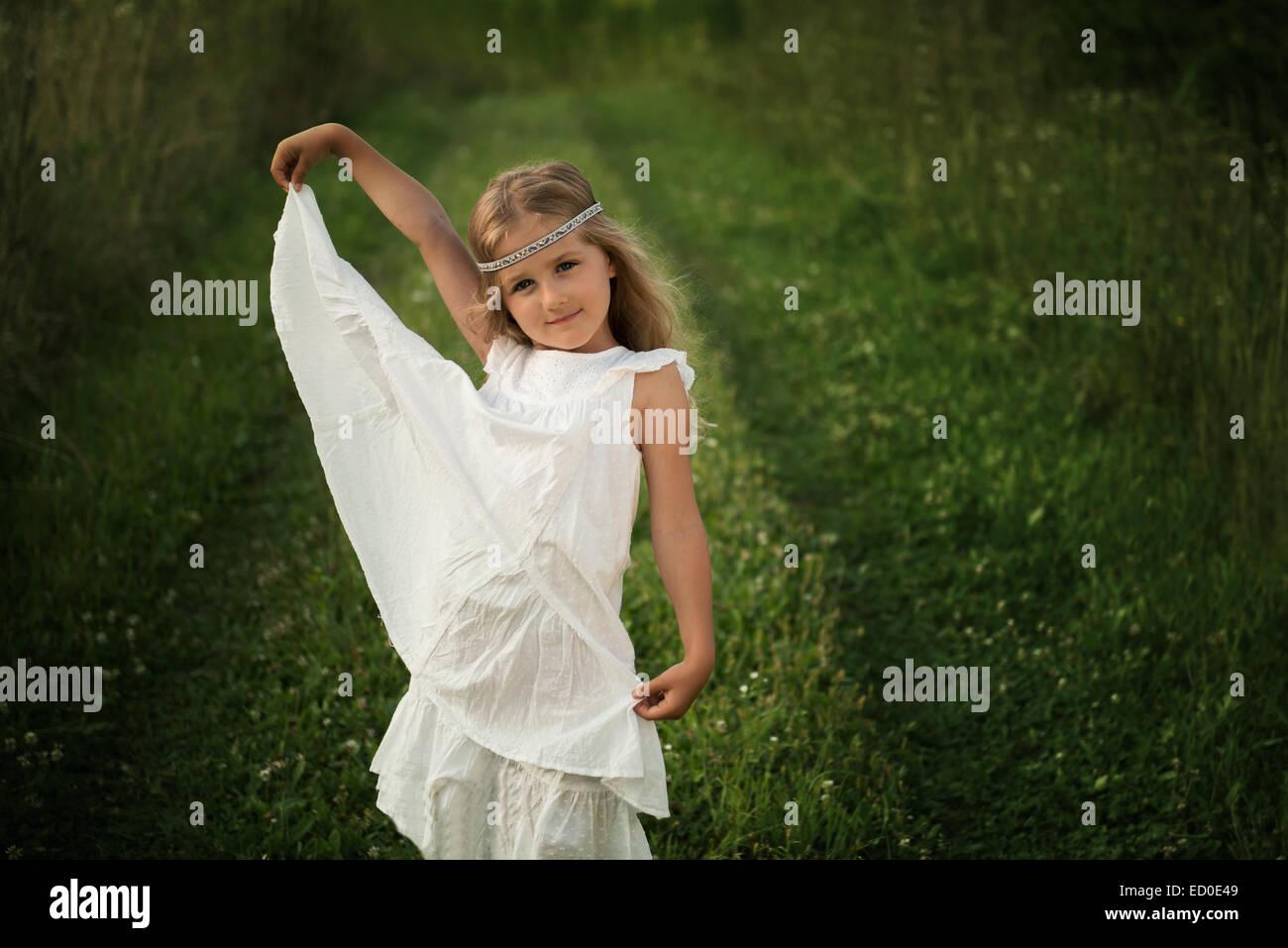 Junges Mädchen (4-5) posiert in langen weißen Kleid Stockbild