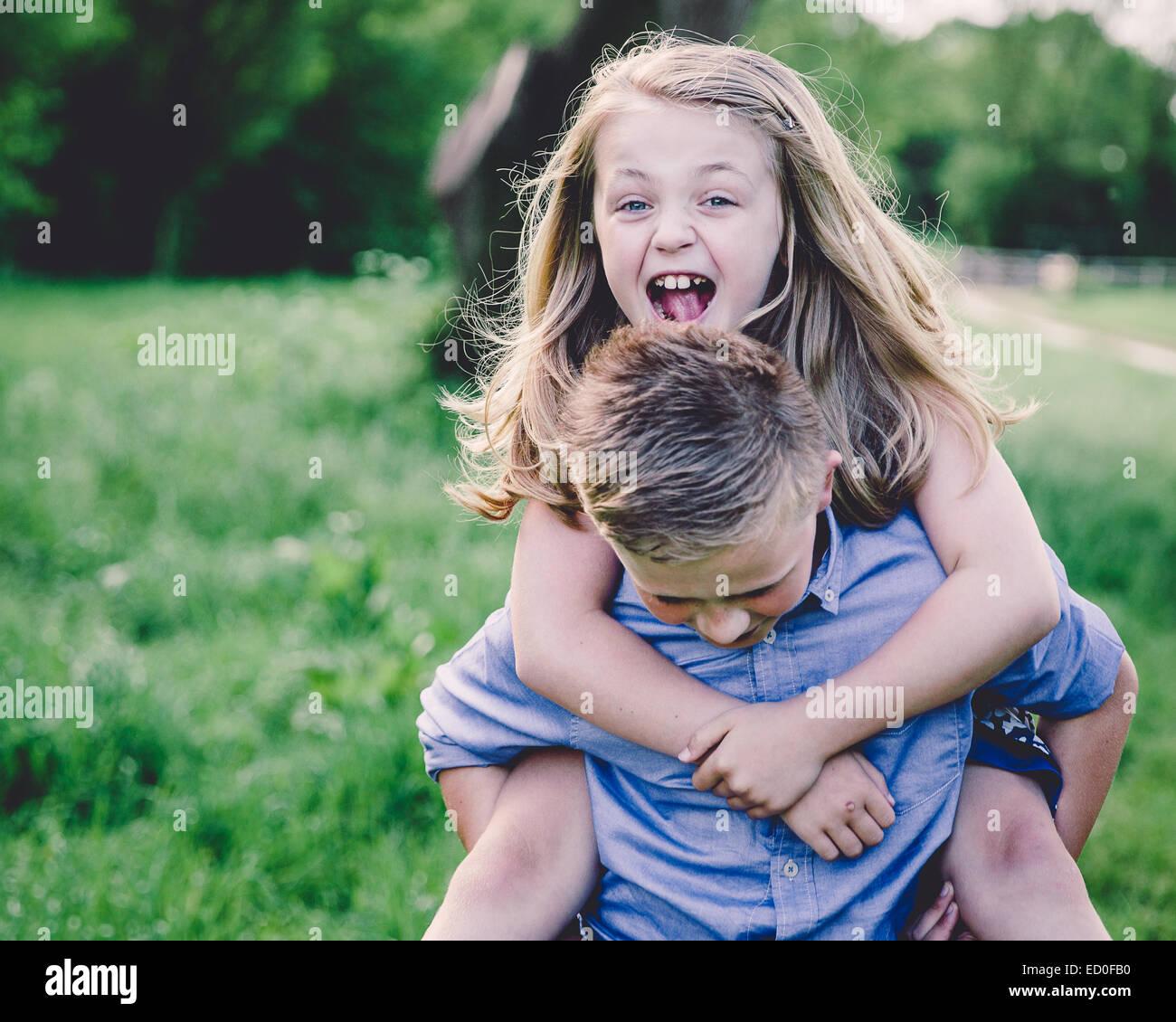 Geschwister (8-9, 10-11) vergnügen sich im Lande Stockbild