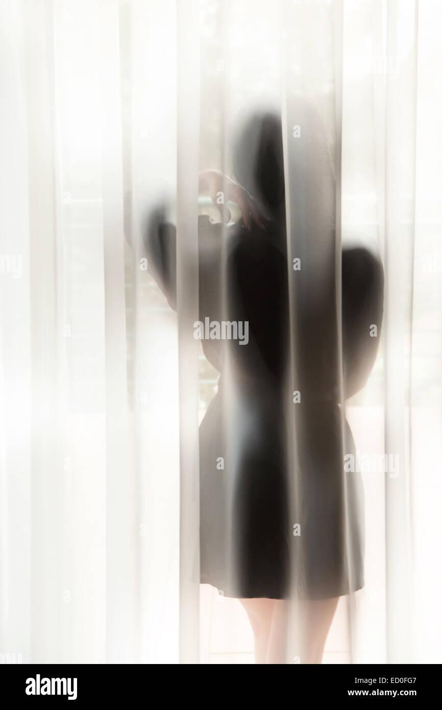 Frau hinter Vorhang Blick durch Fenster Stockbild